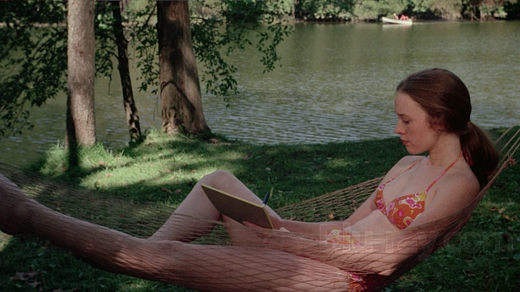 Camille Keaton in I Spit On Your Grave. Jennifer lounges in a hammock next to a lake, wearing a floral orange and pink bikini. She is concentrating on her writing, holding a notepad and pen.